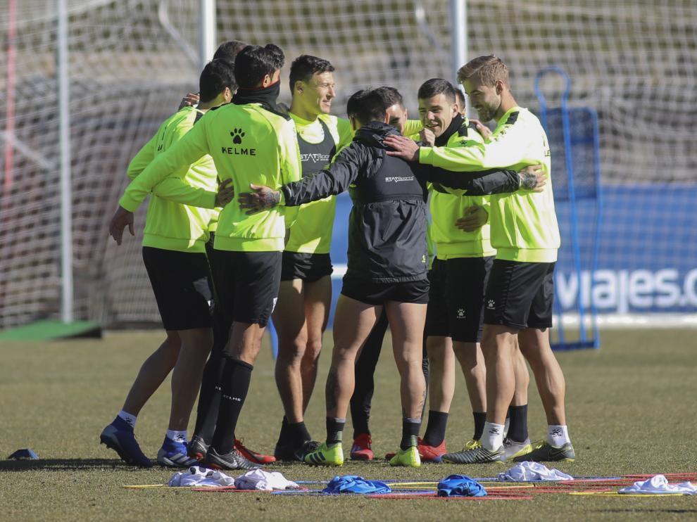Los jugadores de la SD Huesca realizan un corro en el césped del IES Pirámide.