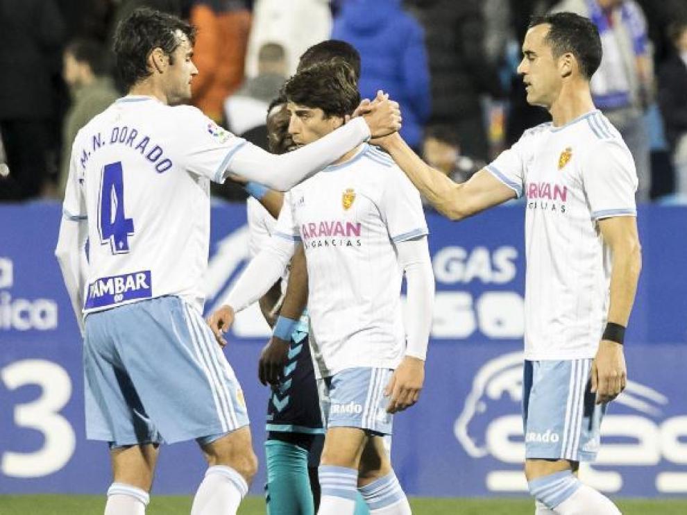 Dorado (4) saluda a Linares (7) al término del partido de este sábado entre el Real Zaragoza y el Albacete en La Romareda. Ambos, refuerzos de invierno, son los últimos en debutar con el equipo esta temporada.