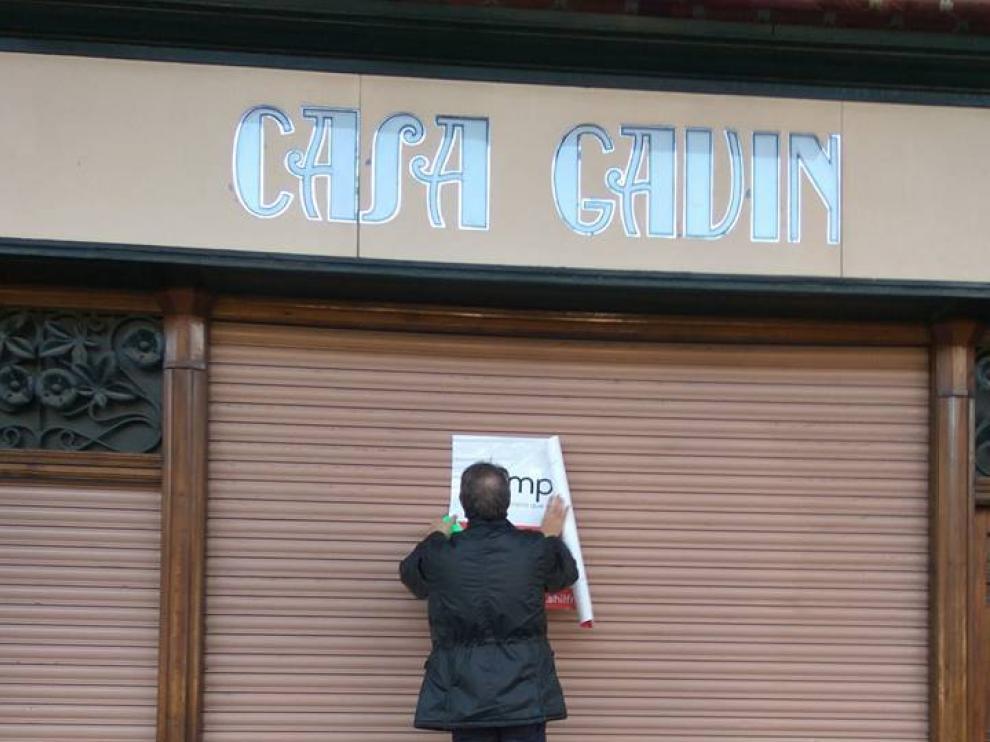Un empleado de la inmobiliaria, colgando el cartel en el que se anuncia la venta del local de Casa Gavín.