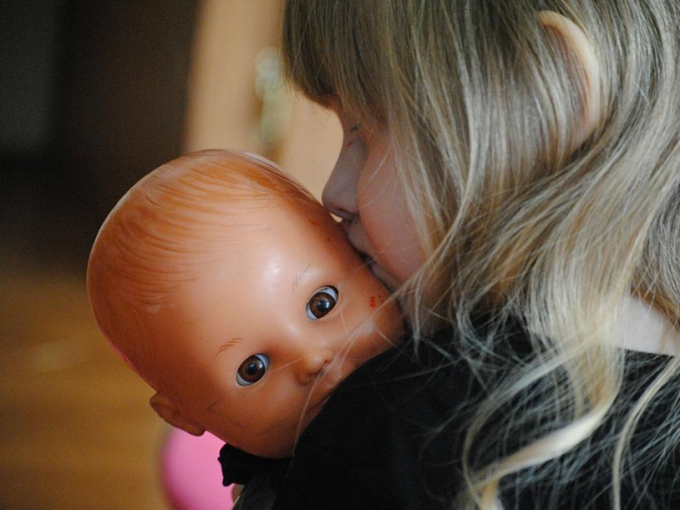 Una niña juega con su muñeca
