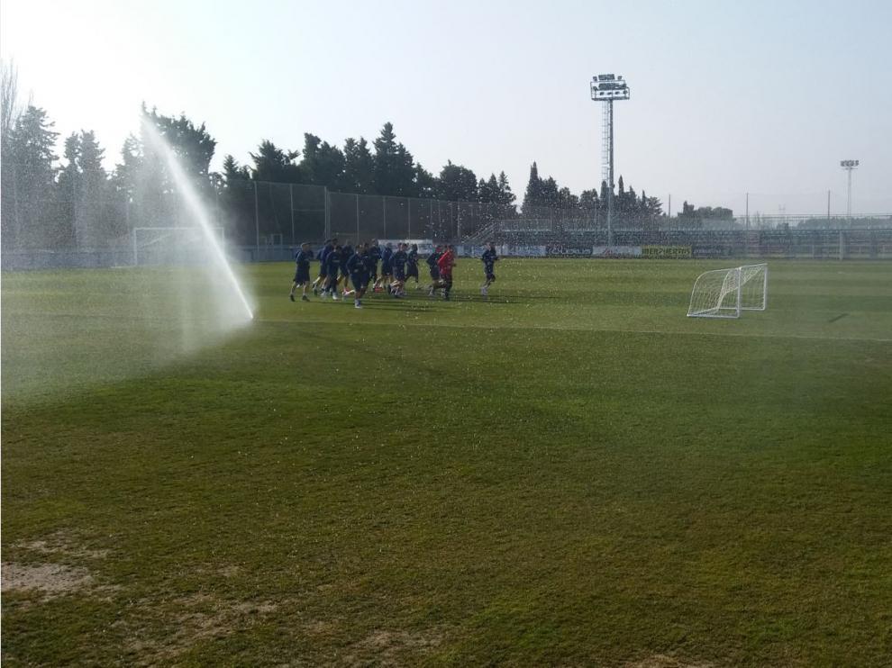 El grupo de jugadores del Real Zaragoza, al inicio del entrenamiento de este martes entre los aspersores de la Ciudad Deportiva.