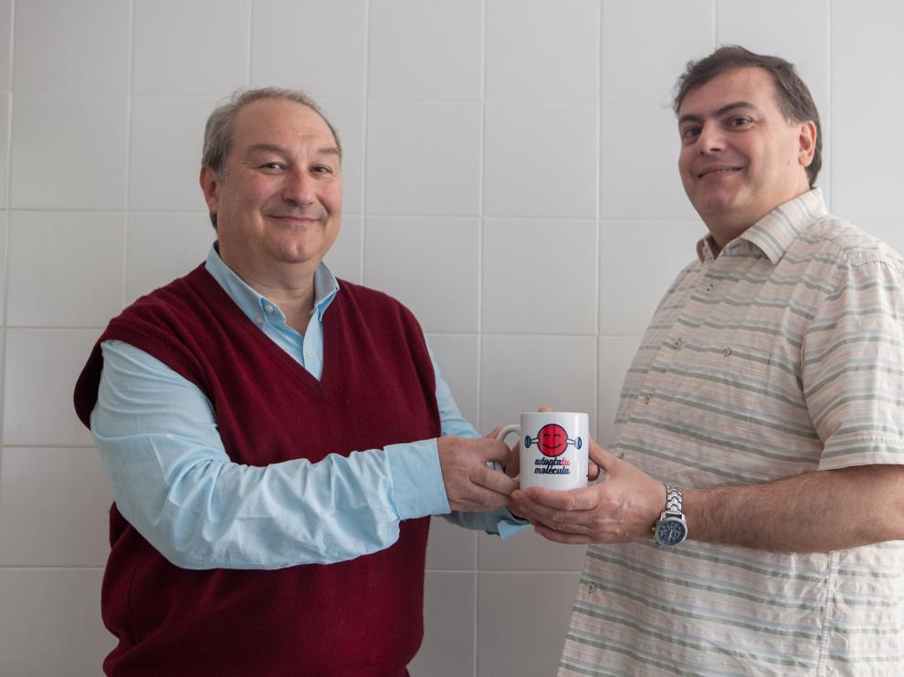 José Ignacio García Laureiro (izda.), haciendo entrega de una de las tazas de 'moleculica' a un ganador del concurso de Tercer Milenio 'Adopta tu molécula'