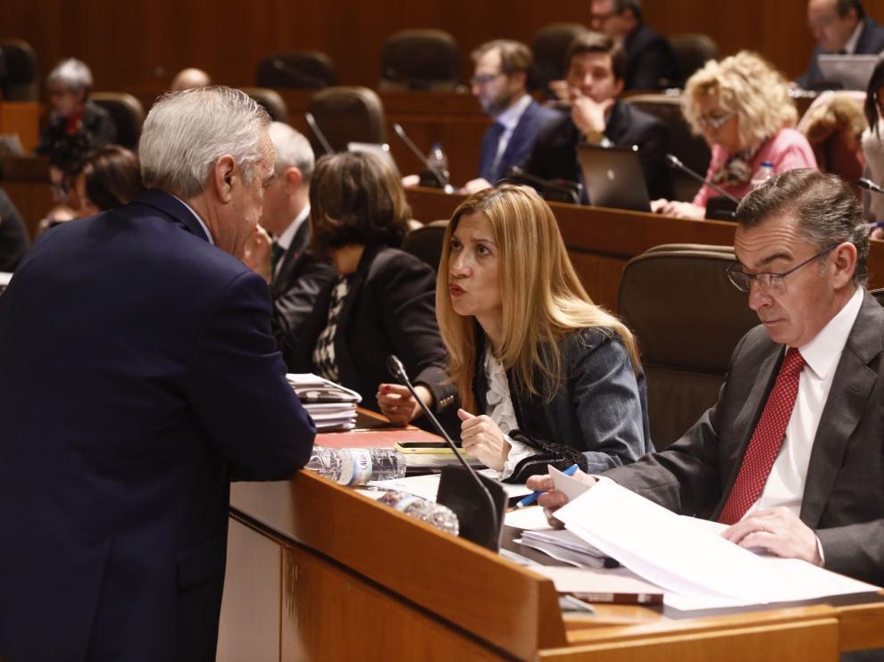 Los portavoces del PSOE y PP, Javier Sada y Mar Vaquero, conversan en el pleno de las Cortes, este jueves.