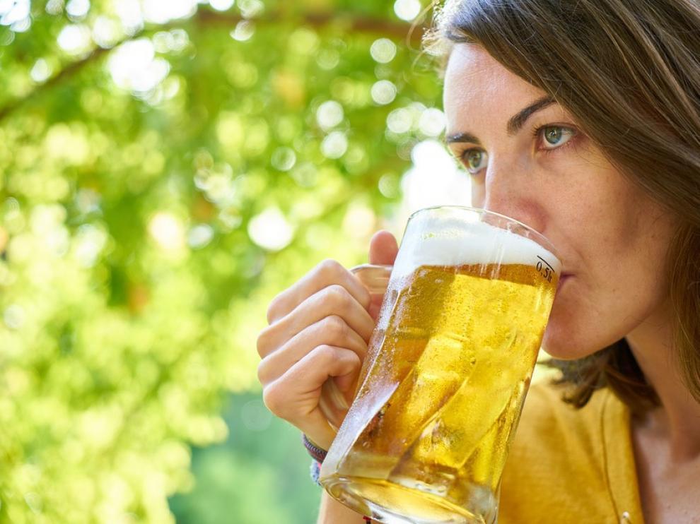 Una mujer se toma una jarra de cerveza.