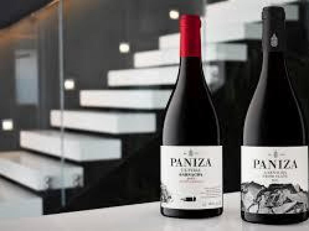 Vinos de Bodegas Paniza con las instalaciones de la nueva bodega al fondo.