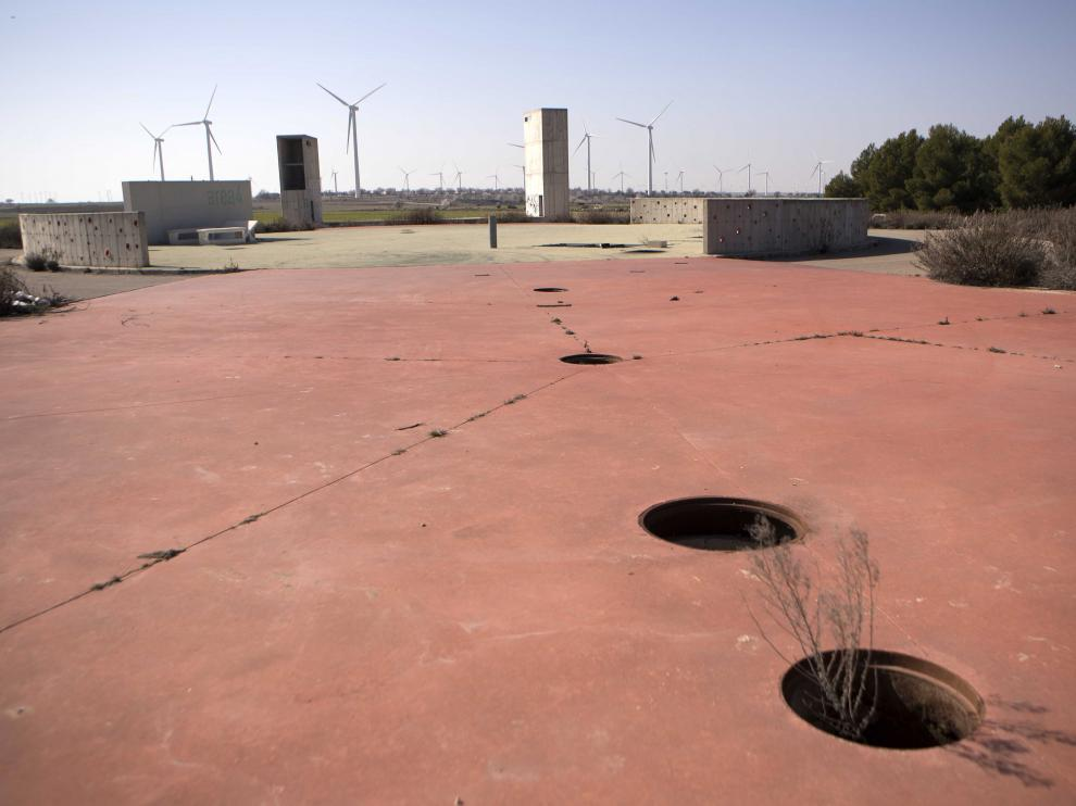 Hilera de alcantarillas sin tapa en uno de los espacios centrales de la urbanización, con los molinos al fondo.