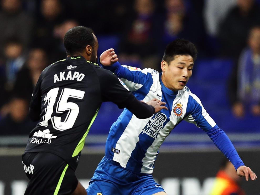 Akapo trata de robarle el balón a Wu Lei.