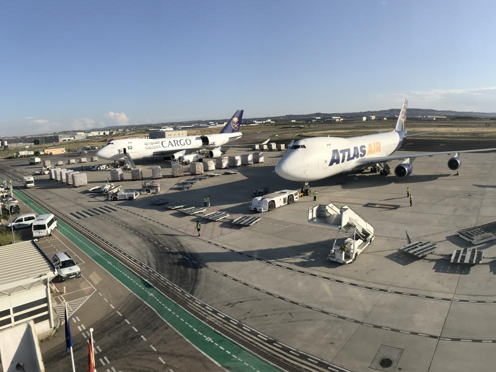 Panorámica de la plataforma de estacionamiento del aeropuerto, con varios aviones de mercancías y uno de pasajeros.