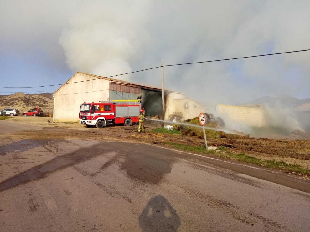 Los bomberos han sacado al exterior un centenar de balas de paja que estaban ardiendo.