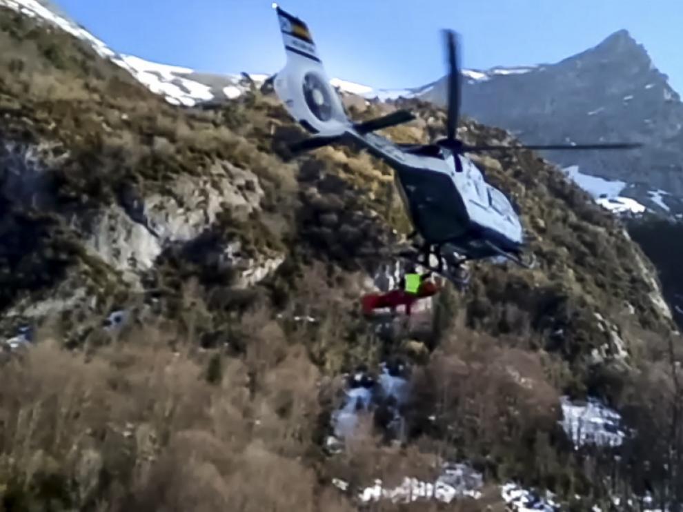 Una imagen de la camilla con el herido siendo izada al helicóptero
