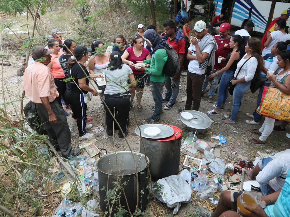 Un grupo de personas reparte comida en la frontera entre Venezuela y Colombia.