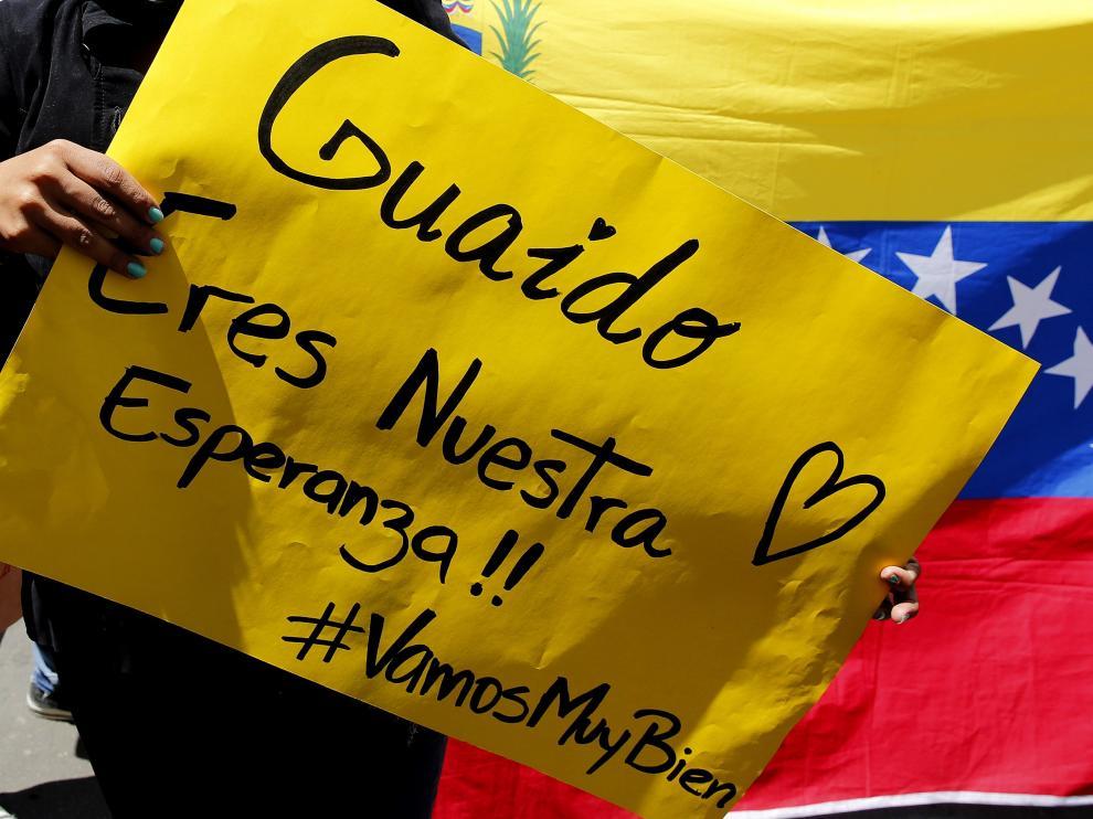 Una mujer sostiene un cartel durante una concentración de venezolanos en Colombia, donde se celebra este lunes la reunión de la cumbre del Grupo de Lima sobre Venezuela.