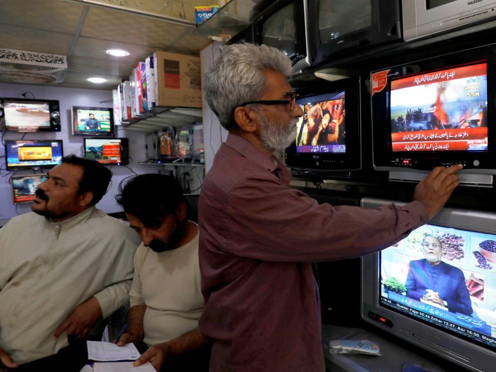 Un hombre mira la televisión que informa del derribo de los cazas indios.