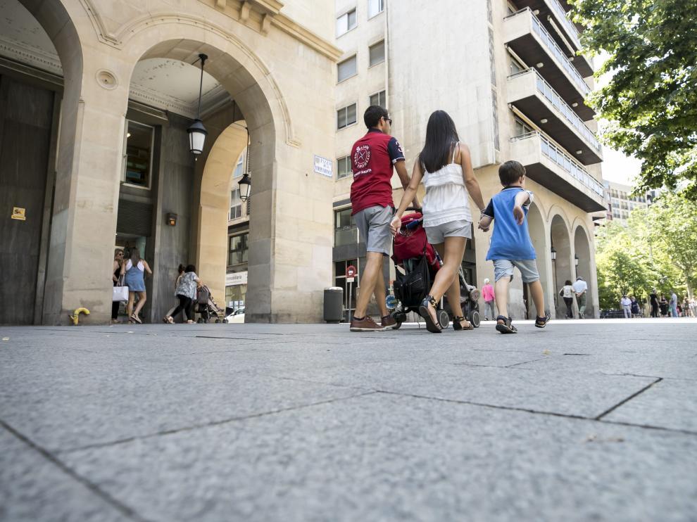 Una pareja pasea con sus hijos por Zaragoza.