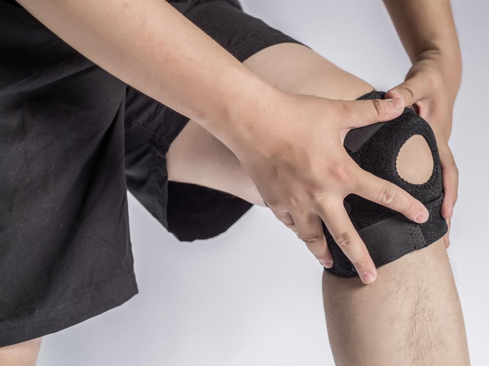 Close-up Of A Man Wearing Knee Brace Over White Background