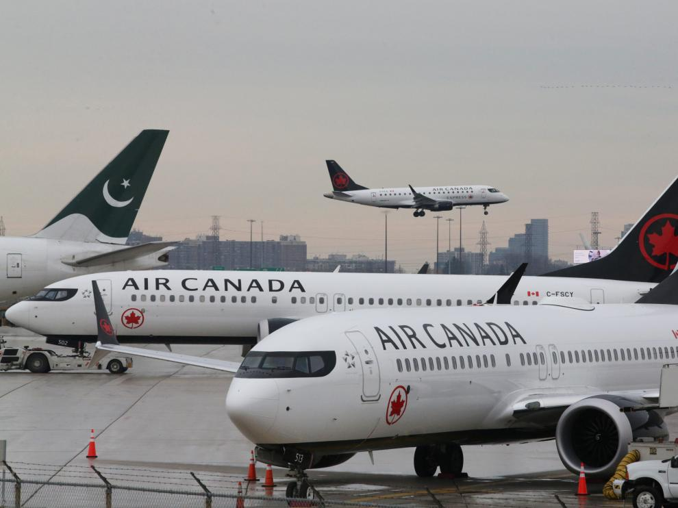 Two Air Canada Boeing 737 MAX 8 aircrafts are seen on the ground as Air Canada Embraer aircraft flies in the background at Toronto Pearson International Airport in Toronto, Ontario, Canada, March 13, 2019.  REUTERS/Chris Helgren [[[REUTERS VOCENTO]]] ETHIOPIA-AIRPLANE/CANADA