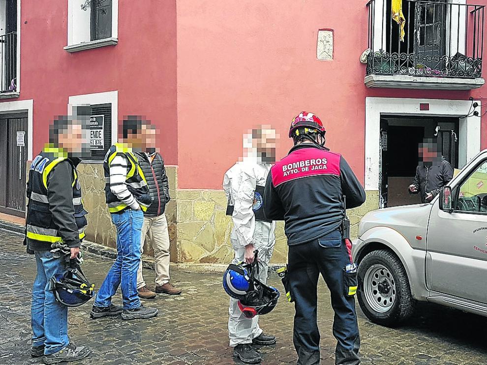 Bomberos y agentes de la Policía Científica acceden al edificio para la investigación.