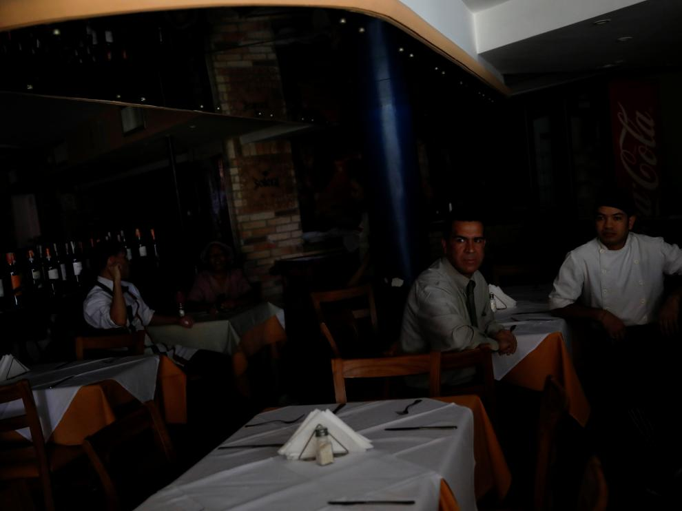 Workers wait for clients at a restaurant during a blackout in Caracas, Venezuela March 25, 2019. REUTERS/Carlos Garcia Rawlins [[[REUTERS VOCENTO]]] VENEZUELA-POLITICS/BLACKOUT