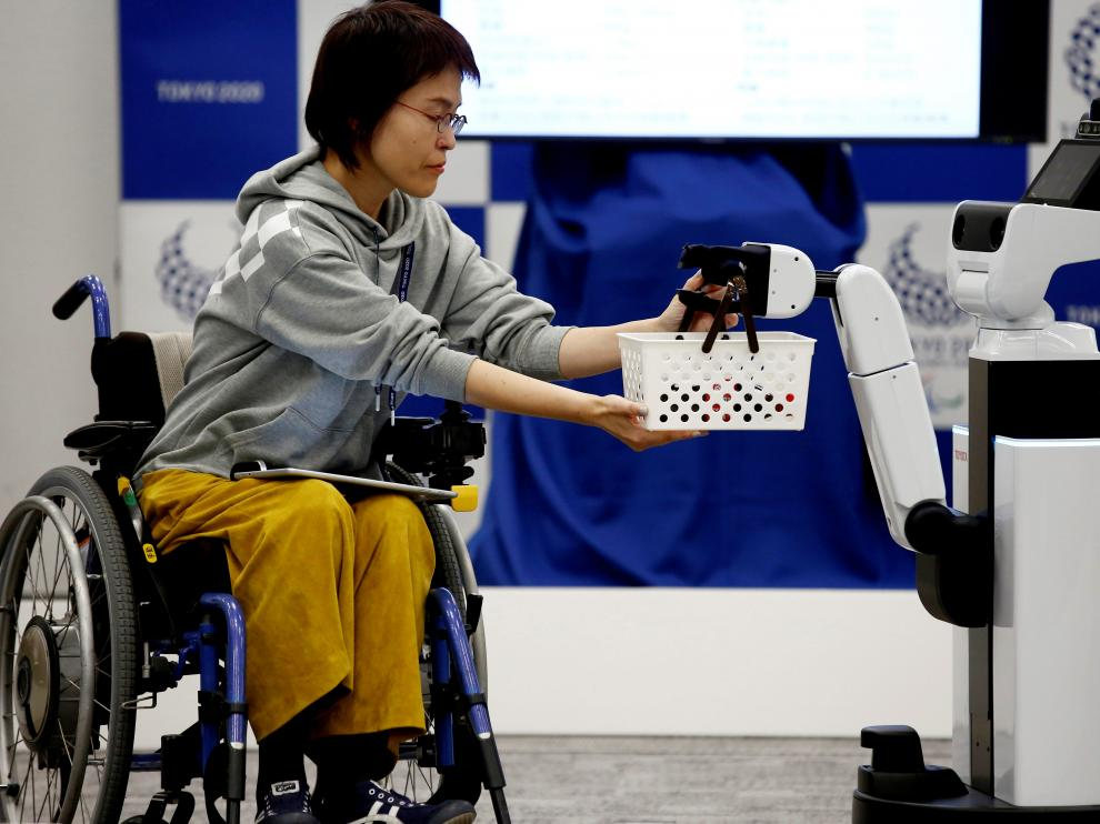 Toyota's Human Support Robot (HSR) delivers a basket to a woman in a wheelchair at a demonstration of Tokyo 2020 Robot Project for Tokyo 2020 Olympic Games in Tokyo, Japan, March 15, 2019. REUTERS/Kim Kyung-hoon [[[REUTERS VOCENTO]]] OLYMPICS-2020/ROBOTS