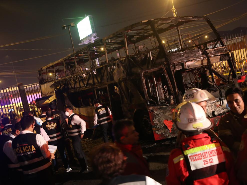 El autobús completamente calcinado en la estación informal de Lima (Perú).