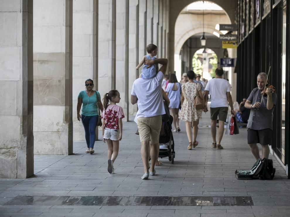 Un padre pasea con sus hijos por Zaragoza.