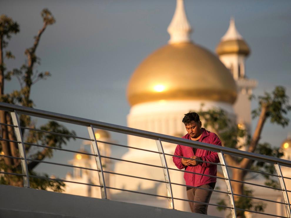 Un hombre camina frente a la mezquita del sultán Omar Ali Saifuddien, en Bandar Seri Begawan, Brunéi.