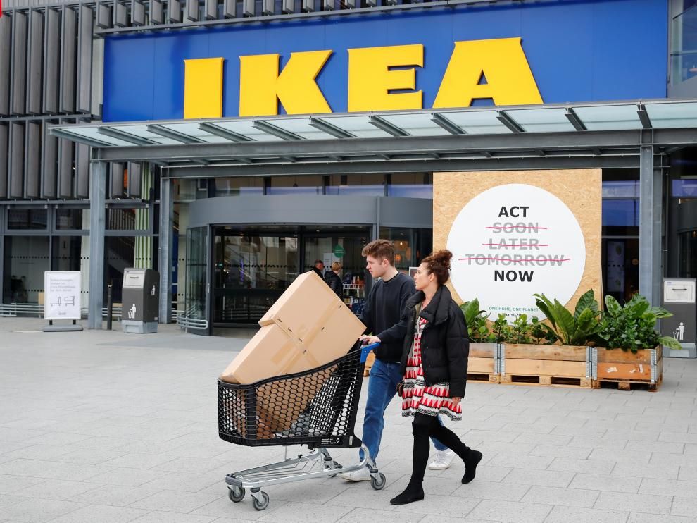 """Customers walk by a placard reading """"Act Now"""" as they leave the IKEA store in Kaarst near Duesseldorf, Germany, April 3, 2019. REUTERS/Wolfgang Rattay [[[REUTERS VOCENTO]]] IKEA-SUSTAINABILITY/CITIES"""