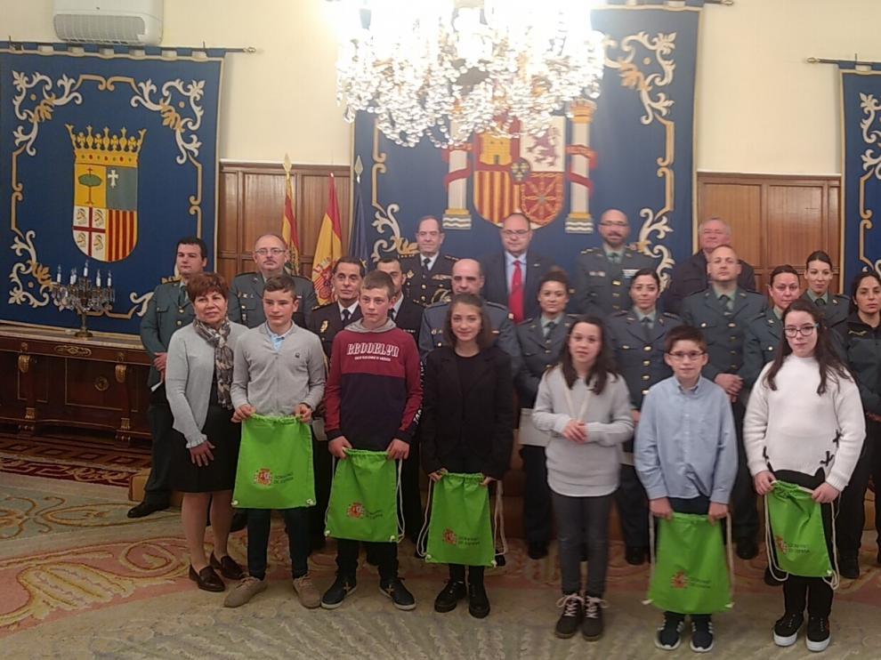 Foto de familia con niños del CRA de Rubielos, los agentes galardonados y las autoridades.