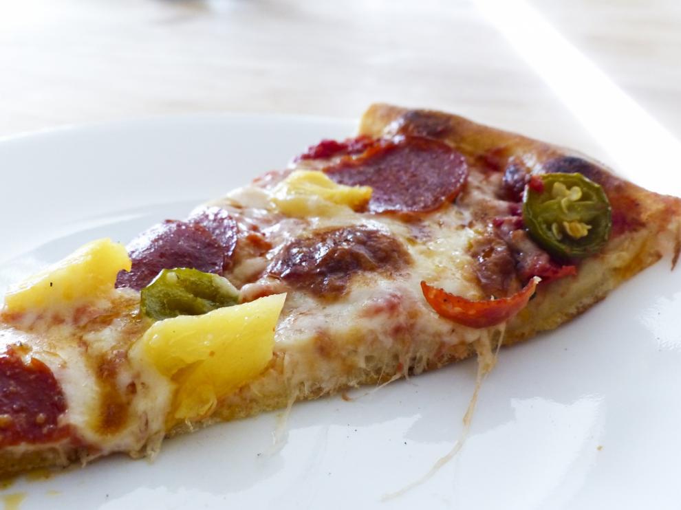 Sí, esto es una foto de trozo de pizza con piña.
