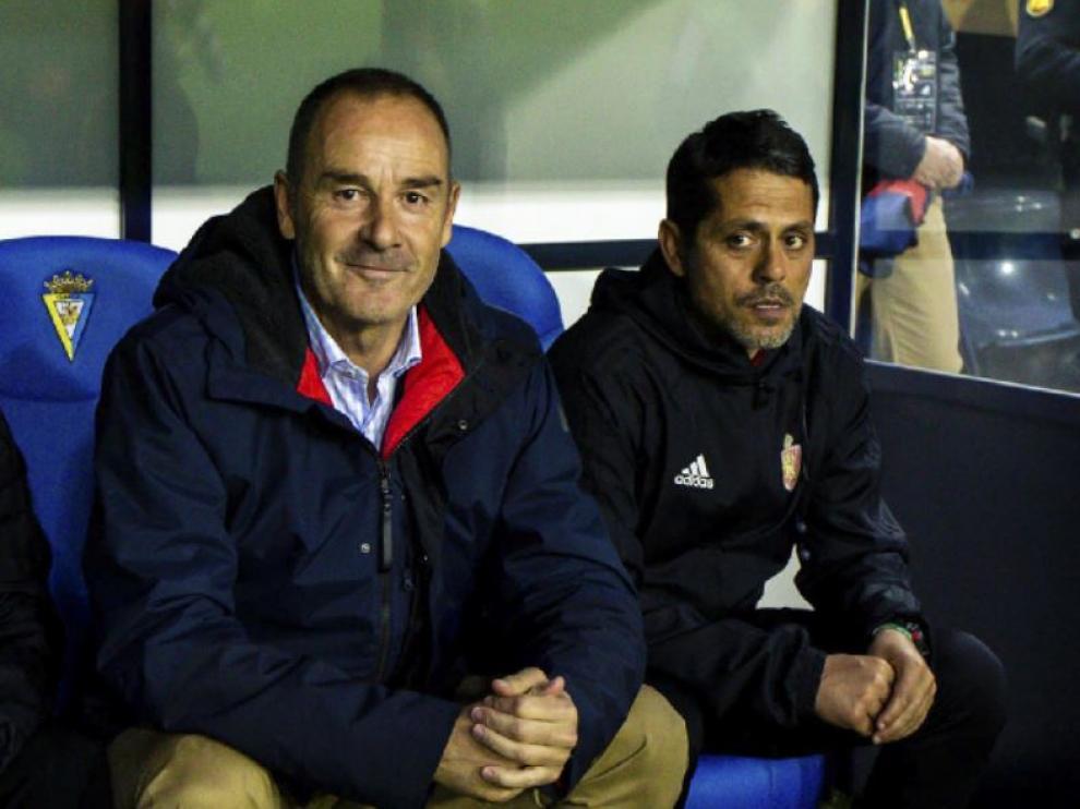 Víctor Fernández, sonriente junto a su ayudante, José Luis Loreto, en el partido Cádiz-Real Zaragoza de la noche de este lunes.