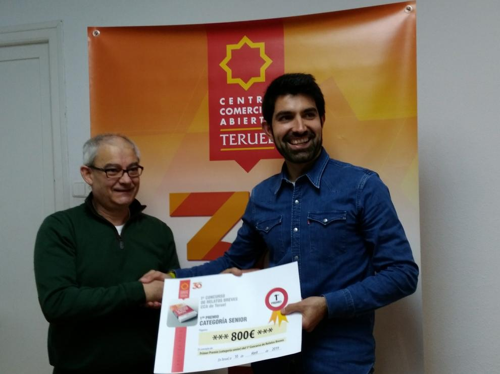 javier Gómez, del Centro Comercial Abierto, entrega el premio de relatos a Javier Lizaga.