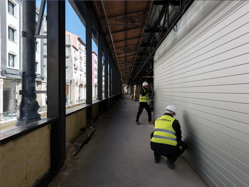 Varios operarios colocando ya las persianas de la empresa aragonesa Ferpal en el Mercado Central de Zaragoza