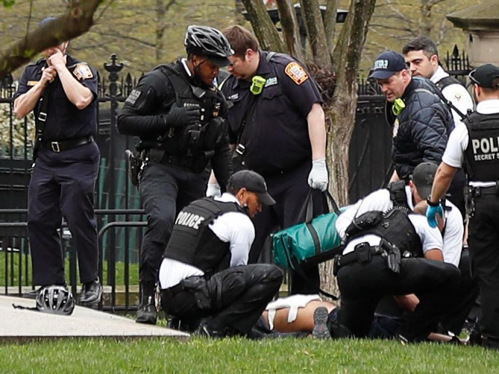 Policía y efectivos de emergencias asisten al hombre que ha intentado prenderse fuego frente a la Casa Blanca.
