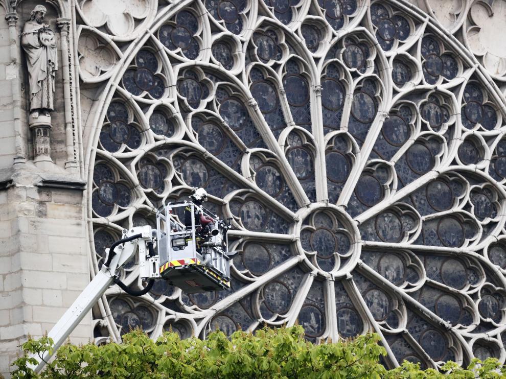 Un bombero trabaja en un elevador junto al rosetón de la catedral de Notre Dame para evaluar los daños.