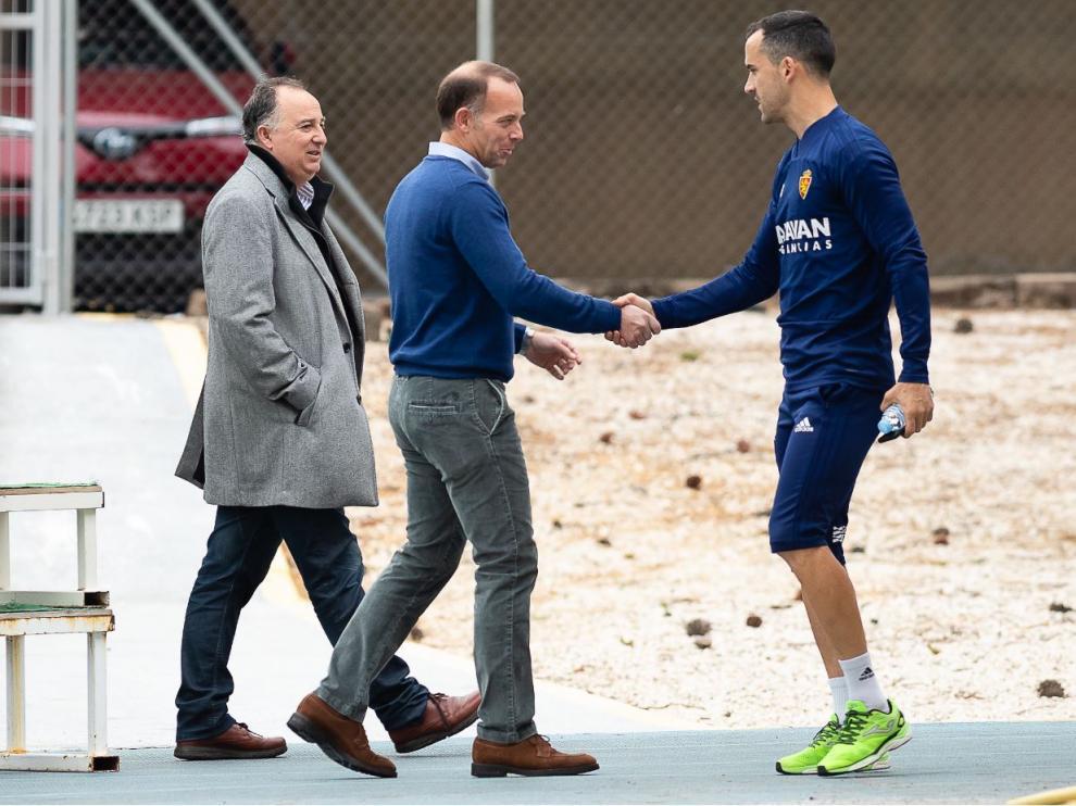 Cristian Lapetra, el presidente del Real Zaragoza, saluda a Miguel Linares en la mañana de este Jueves Santo en la Ciudad Deportiva, acompañado por el responsable de Comunicación del club, Miguel Gay.