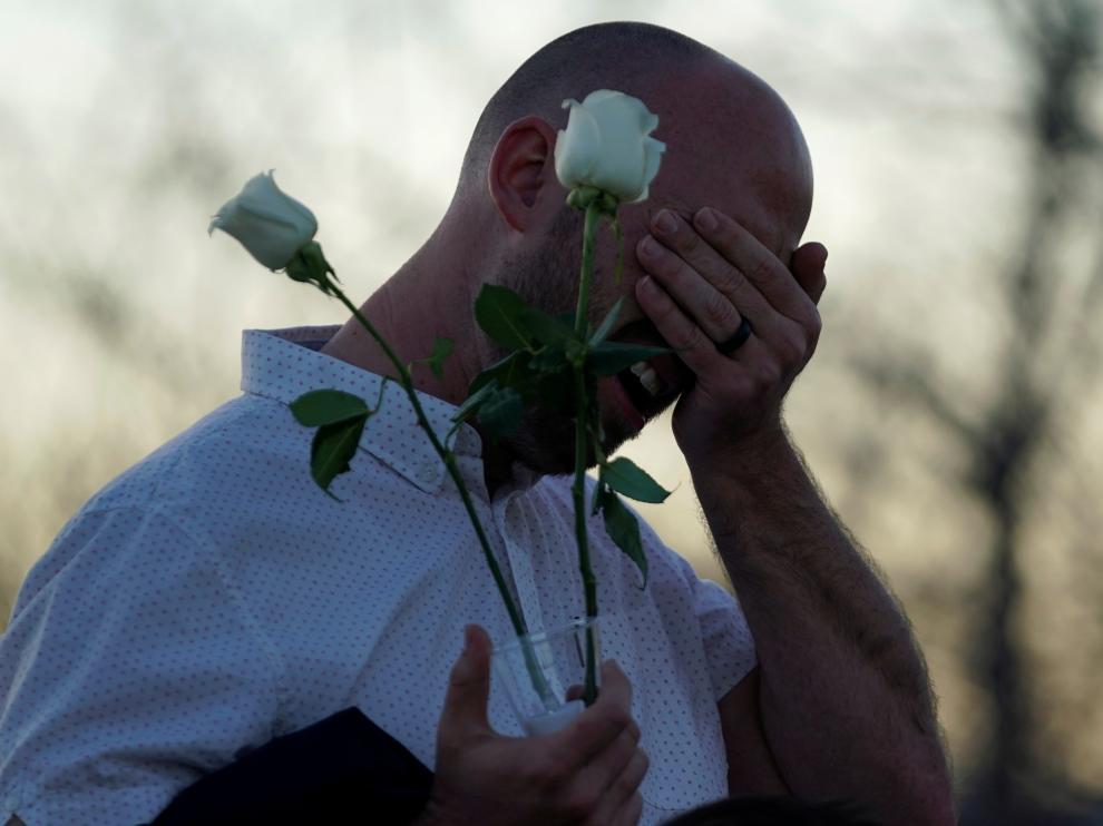 Un superviviente del tiroteo llora ante el memorial que recuerda a las víctimas