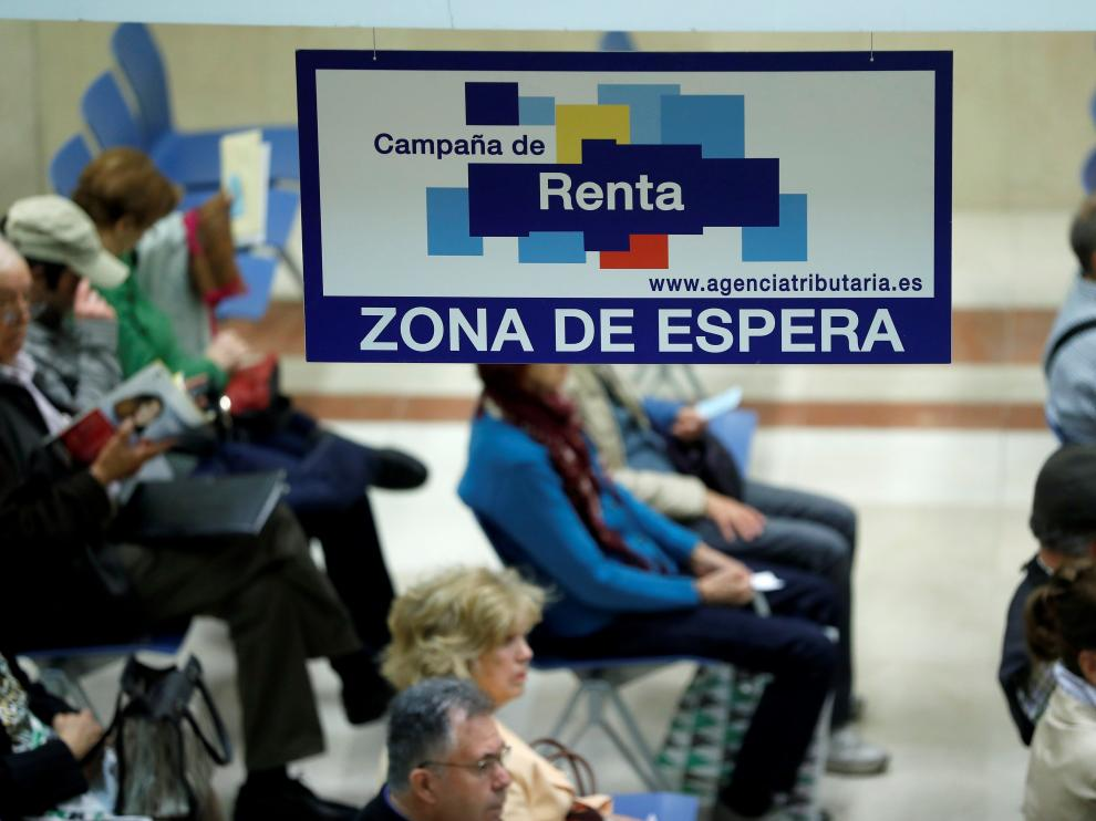 Unos ciudadanos esperan en una delegación madrileña para ser elaborar la declaración de la renta en la campaña pasada.