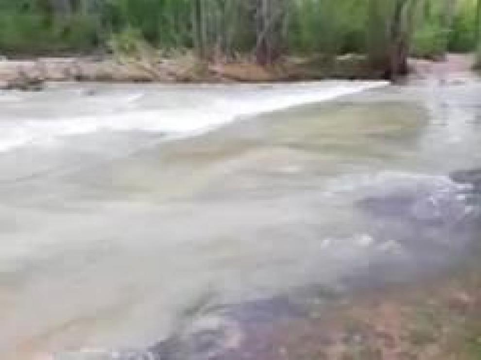 La crecida del río Mijares a su paso por la localidad turolense de Olba ha dejado a los vecinos del barrio de los Tarrasones aislados, sin poder salir de sus casas.