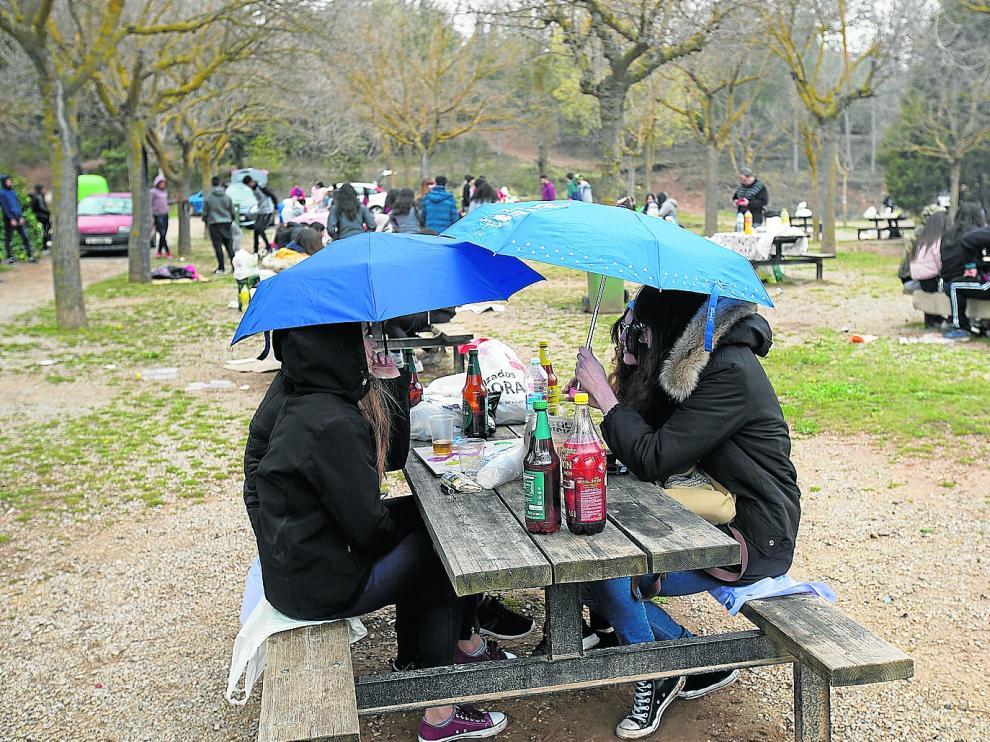 La lluvia obligó a sacar el paraguas en la Fuente Cerrada, el paraje preferido por los turistas para celebrar la fiesta.