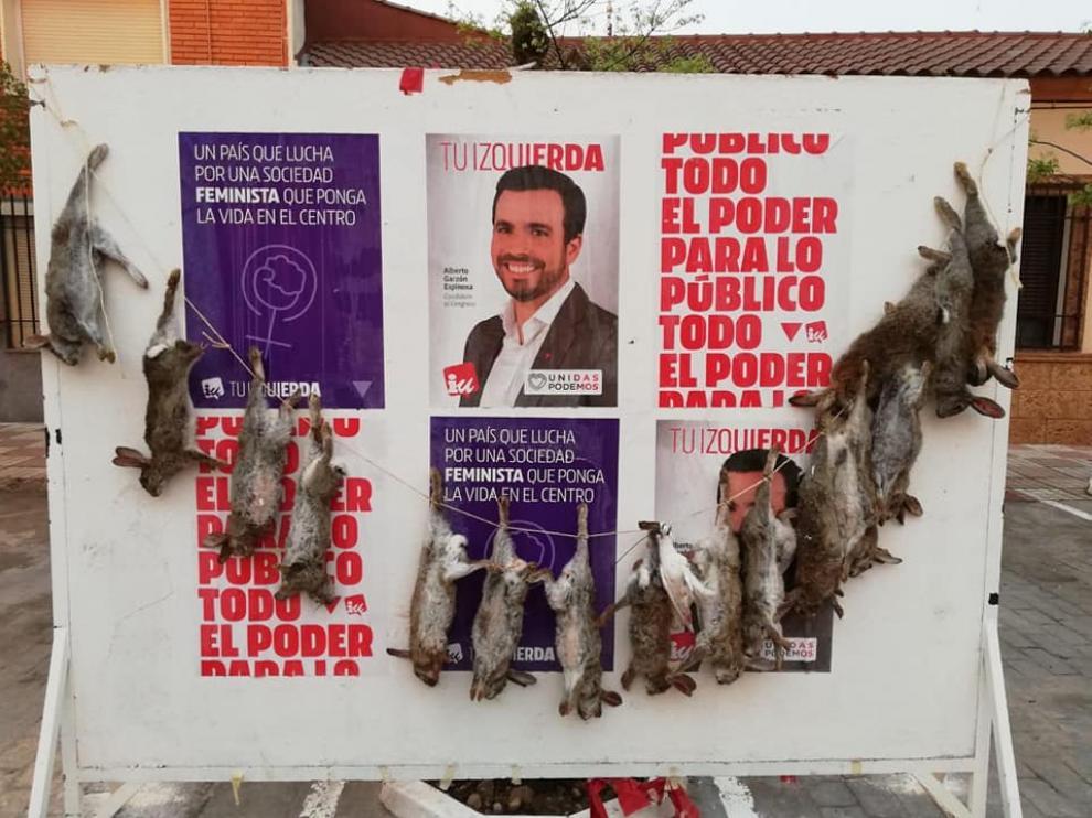 Conejos muertos colgados sobre los carteles de Unidas Podemos en La Puebla de Almoradiel (Toledo).
