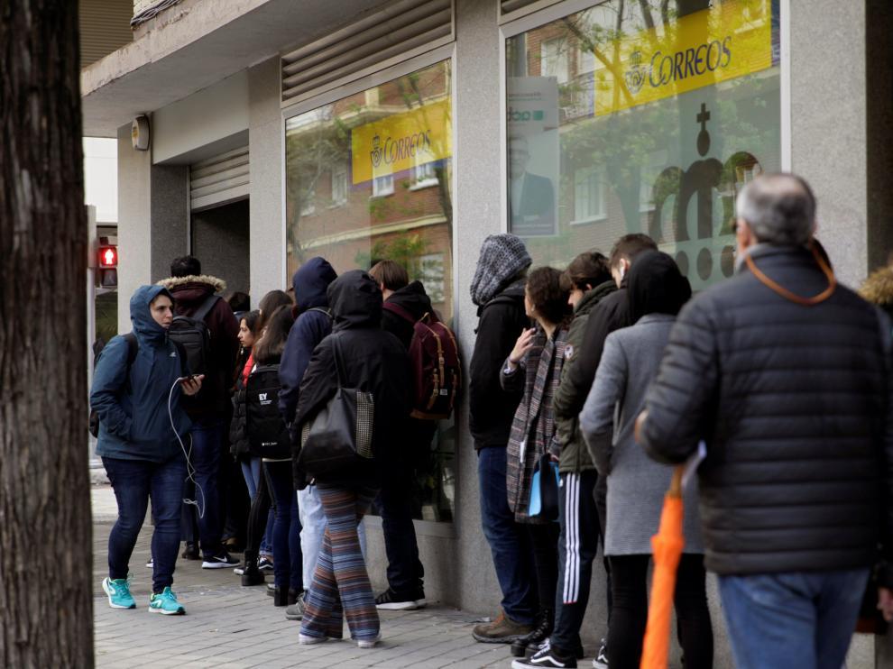 Largas colas de ciudadanos para ejercer el derecho al voto por correo en Madrid.