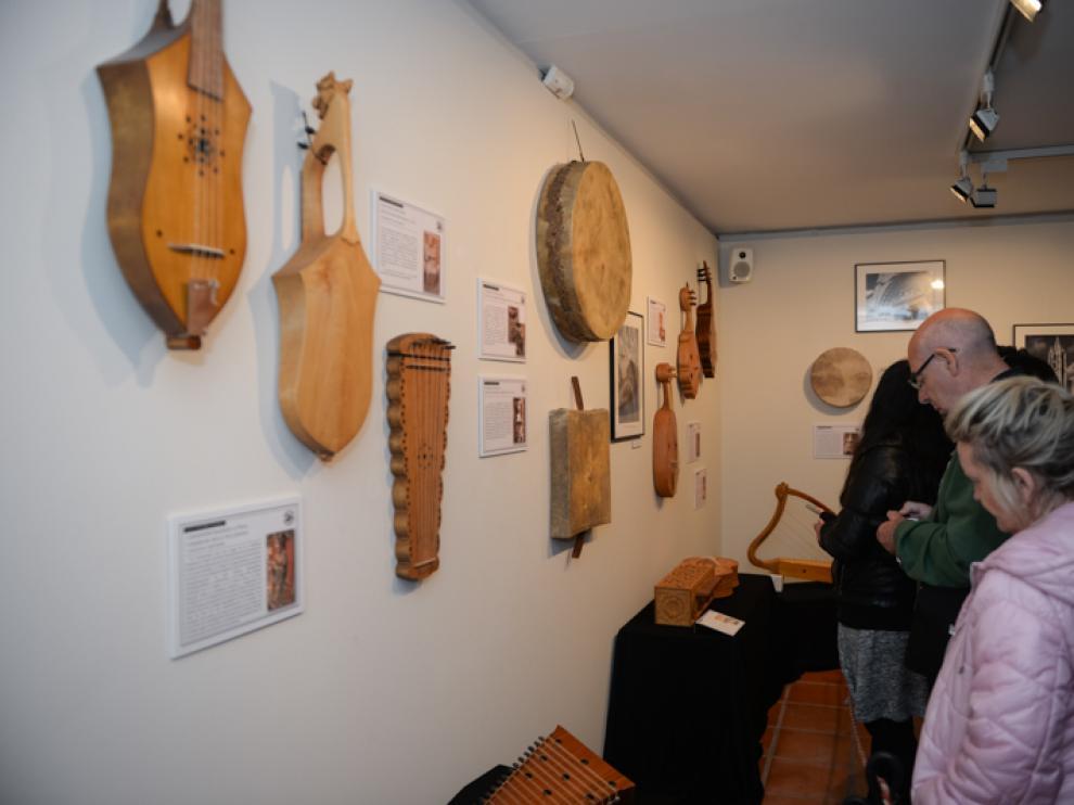 Unos visitantes observan los instrumentos musicales, piezas modernas de modelos antiguos, de la exposicion temporal en el Museo de Albarracín.