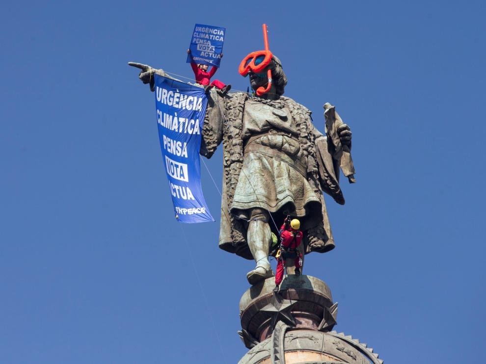 Dos activistas de Greenpeace colocan gafas de buzo a la estatua de Colón para protestar contra el cambio climático.