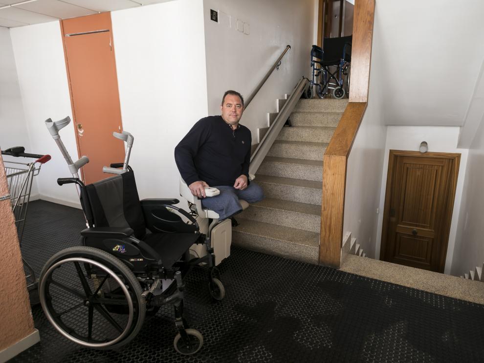 Eugenio, en la silla elevadora que tuvo que instalar para poder acceder a su vivienda.