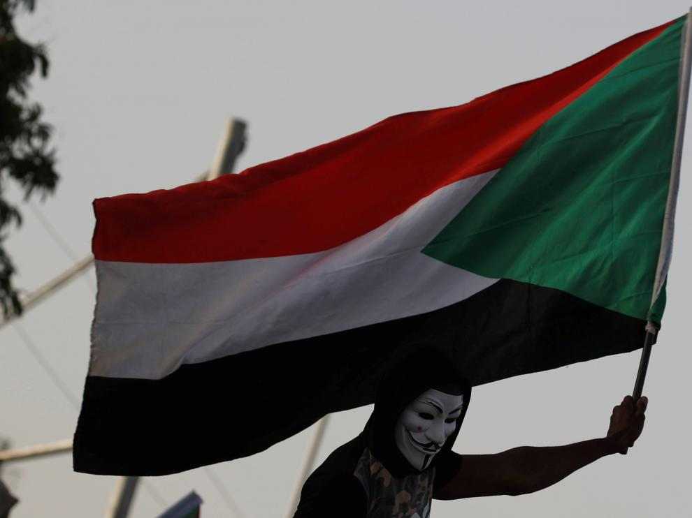 A Sudanese protester, who wears a Guy Fawkes mask, waves a national flag as he attends a demonstration outside the Defence Ministry compound in Khartoum, Sudan, April 29, 2019. REUTERS/Umit Bektas [[[REUTERS VOCENTO]]] SUDAN-POLITICS/