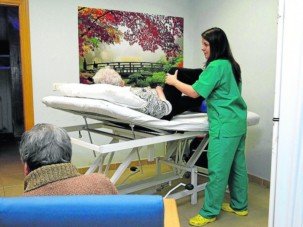 Una cuidadora ayuda a una anciana en el centro de día de Afami en Miranda de Ebro
