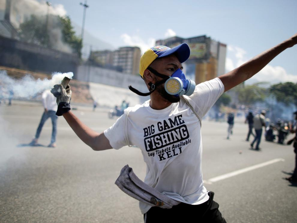 "An opposition demonstrator throws back a tear gas canister on a street near the Generalisimo Francisco de Miranda Airbase ""La Carlota"" in Caracas, Venezuela April 30, 2019. REUTERS/Ueslei Marcelino [[[REUTERS VOCENTO]]] VENEZUELA-POLITICS/"