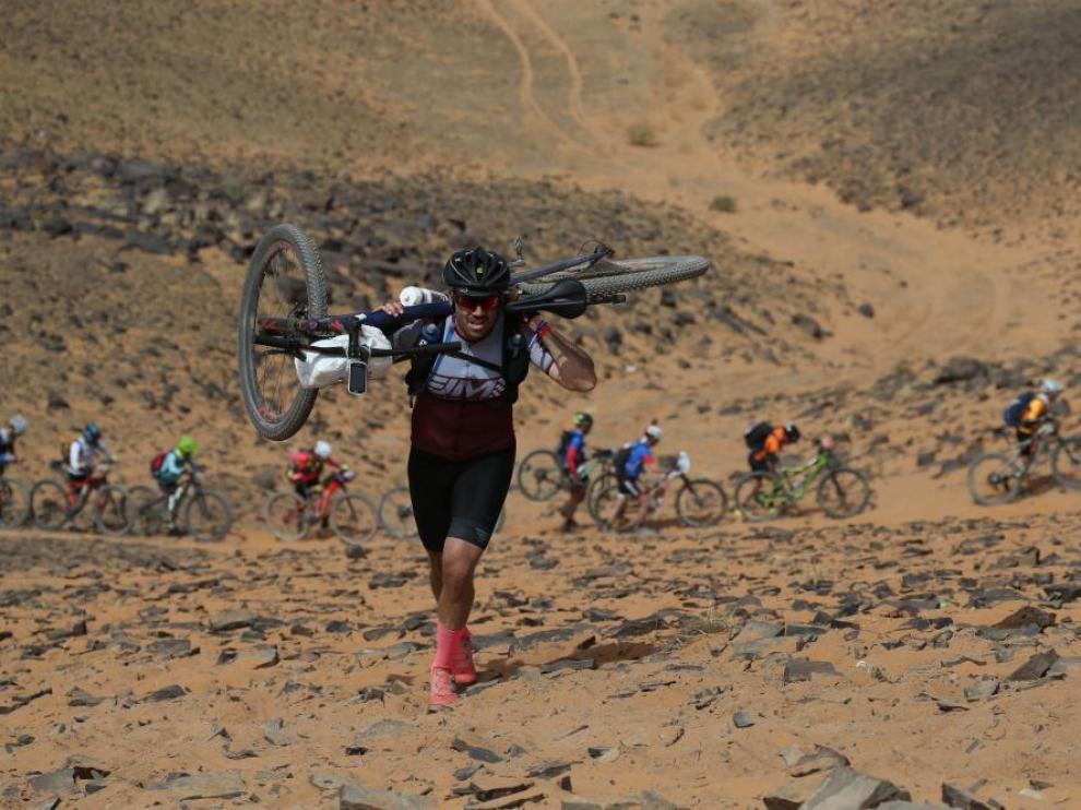 Un ciclista, con la bicicleta a hombros, sube una duna en la Titan Desert 2019.