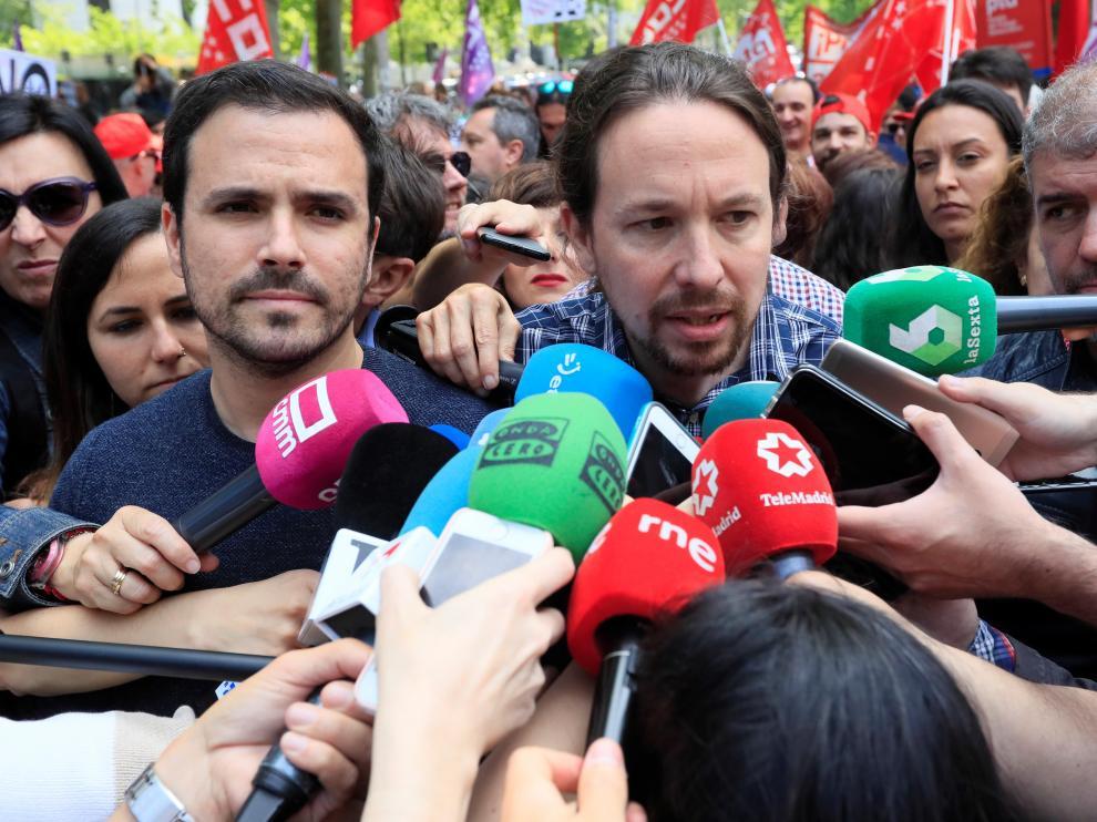 El secretario general de Podemos, Pablo Iglesias (c), en presencia del líder de IU, Alberto Garzón (i), hace declaraciones a los medios antes de participar en la manifestación convocada en Madrid con motivo del Primero de Mayo
