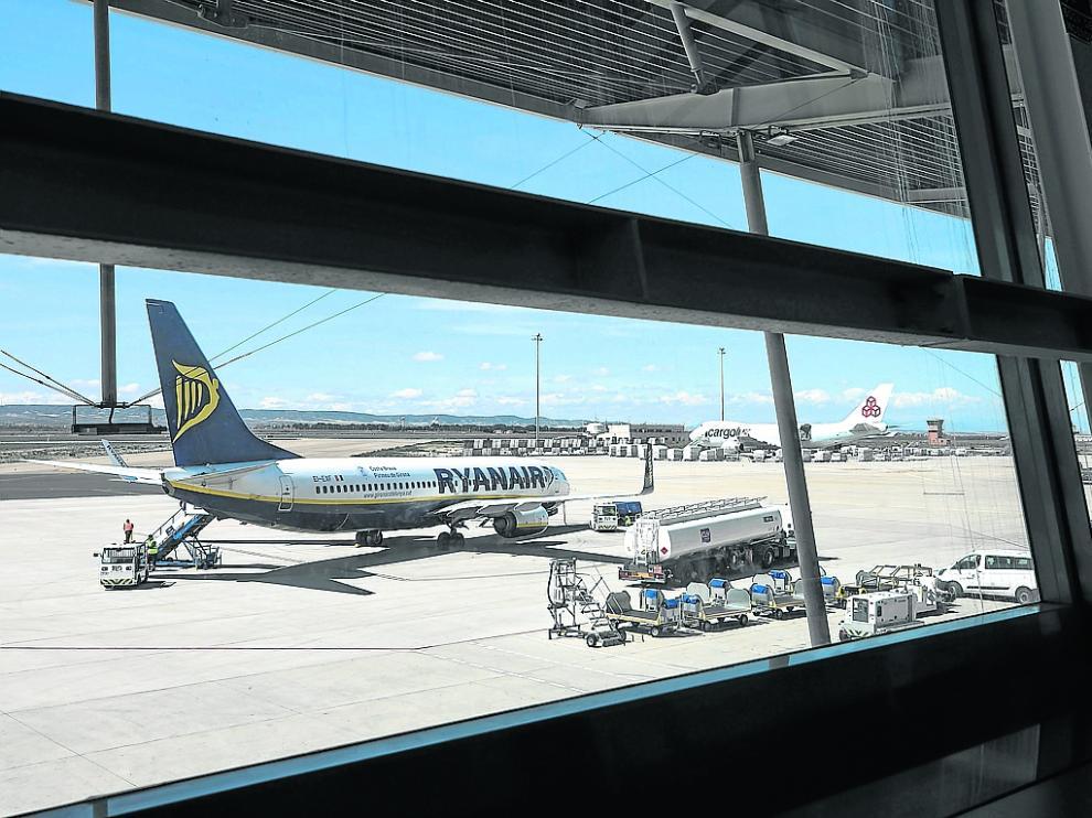 Un avión de pasajeros y otro de carga en el aeropuerto de Zaragoza. Al fondo, la torre de control.